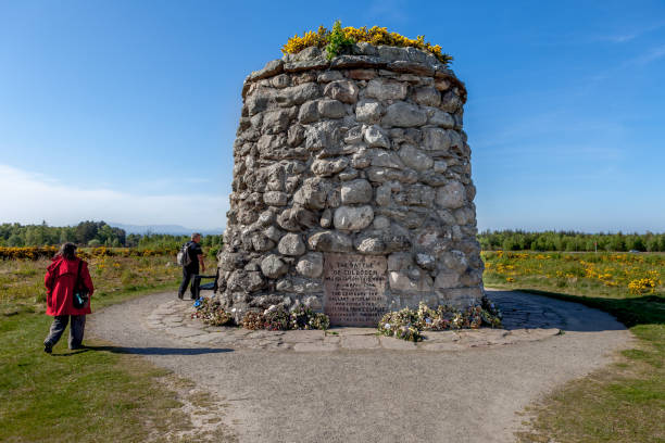 Culloden battlefield memorial cairn in Scotland. Culloden, Scotland - May 02, 2011 : Tourists inspect the Culloden memorial cairn at the  Culloden battlefield in Scotland, UK. culloden stock pictures, royalty-free photos & images