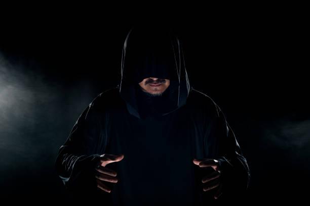 cult leader wearing a dark robe with smoky background - seitas imagens e fotografias de stock