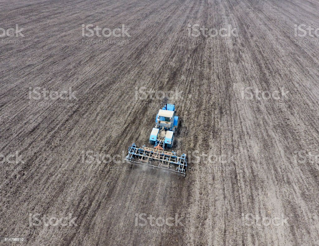 Cultivation of soil for the sowing of cereals. Tractor plows the soil on the field stock photo