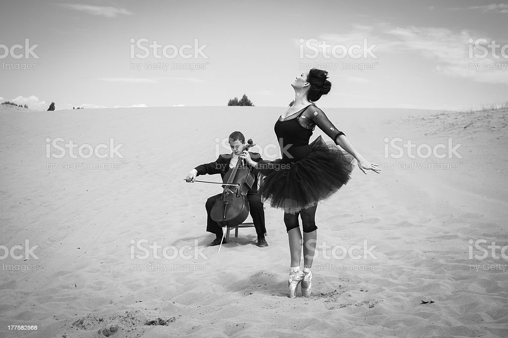 Cultural encounter in the desert A solo cellist plays for an elegant ballerina dancing in the barren desert. 25-29 Years Stock Photo