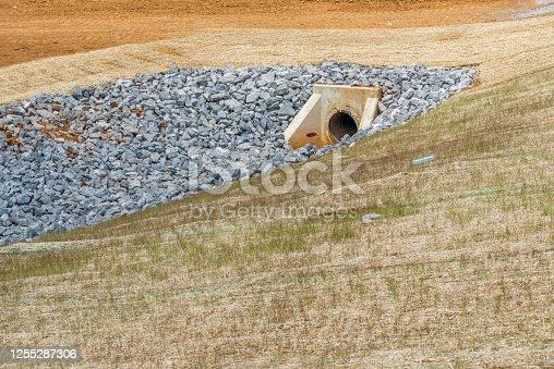 Horizontal shot of a culvert and drainage ditch under construction.