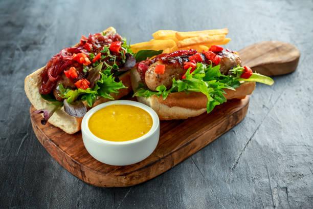 cumberland wurst hotdogs mit karamellisierten zwiebeln, geröstete paprika, pommes frites. - schnelle suppen stock-fotos und bilder