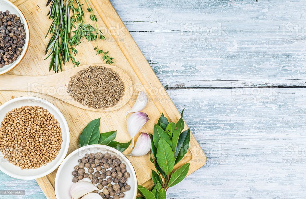 Cumin, rosemary and other spices on wooden background stock photo