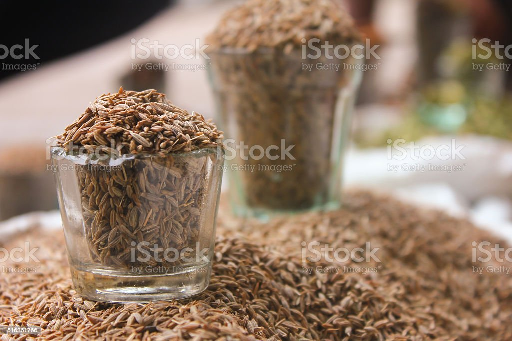 cumin seeds in glass at local market, indian spices stock photo