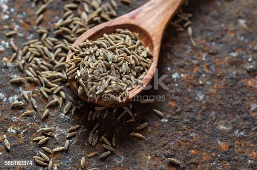 Cumin seeds in wooden spoon on texture background