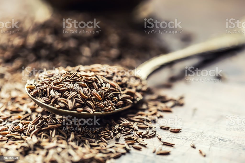 Cumin.Caraway seeds on wooden table. Cumin in vintage bowl. stock photo