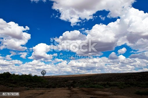 A wide colour image of a sheep farm with dramatic cumulonimbus cloudscape sky with bright blue sky and a windmill windpump windpomp against the horizon Victoria West Great Karoo Central South Africa