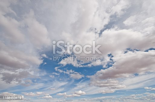 Cumulus clouds appear in a blue sky over Grandview Point in Canyonlands National Park near Moab, Utah, USA.