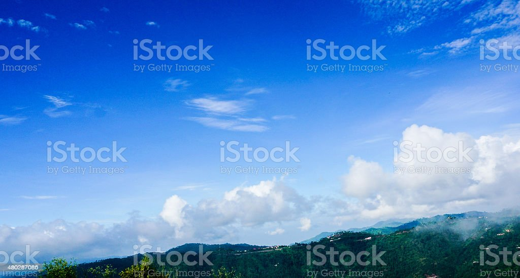 Cumulus clouds with hills and blue sky stock photo