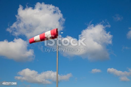 Bright cumulus clouds with striped windsock in clear blue sky at a beach of the Netherlands North Sea region