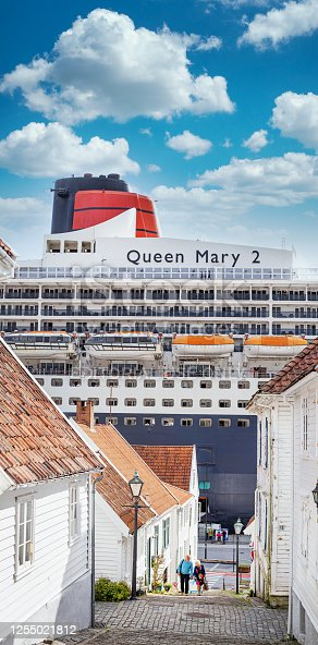 9th August, 2019 - Cunard's flagship, The Queen Mary 2 looming over the pretty cobbled street in the Norwegian town of Stavanger as it is docked while passengers depart and explore the town.