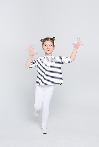 istock Cunning cute little girl showing her palms on white studio background 836547518