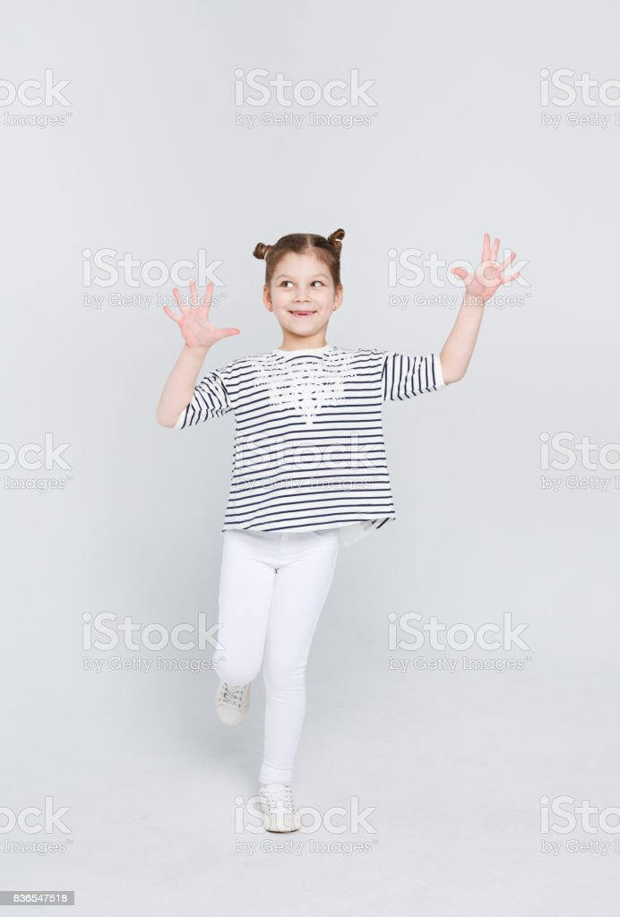 Cunning cute little girl showing her palms on white studio background – zdjęcie