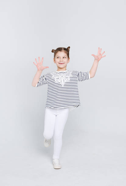 Cunning cute little girl showing her palms on white studio background stock photo