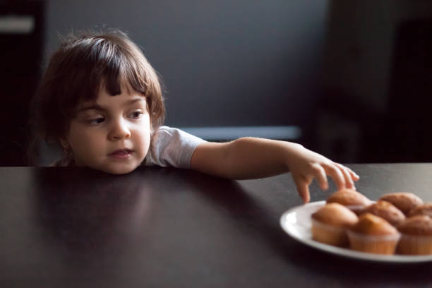 Cunning cute little girl stealing delicious muffin on table stock photo