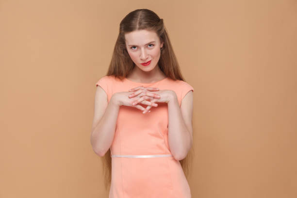 cunning plan, looking at camera. cunning plan, looking at camera. portrait of emotional cute, beautiful woman with makeup and long hair in pink dress. indoor, studio shot, isolated on light brown or beige background. dishonesty stock pictures, royalty-free photos & images