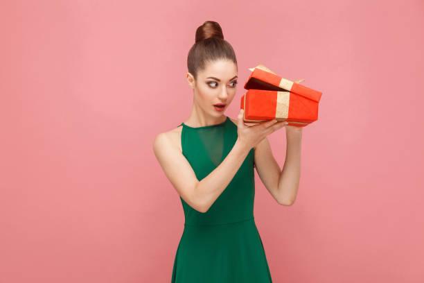 schlaue frau unboxing rote geschenkbox blick ins innere - jugendliche geburtstag geschenke stock-fotos und bilder