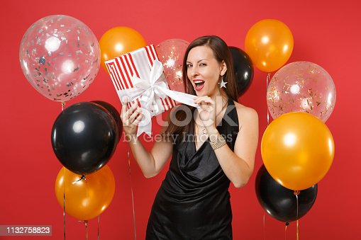 istock Cunning young girl in black dress celebrating opening red box with gift present on bright red background air balloons. International Women's Day, Happy New Year, birthday mockup holiday party concept. 1132758823