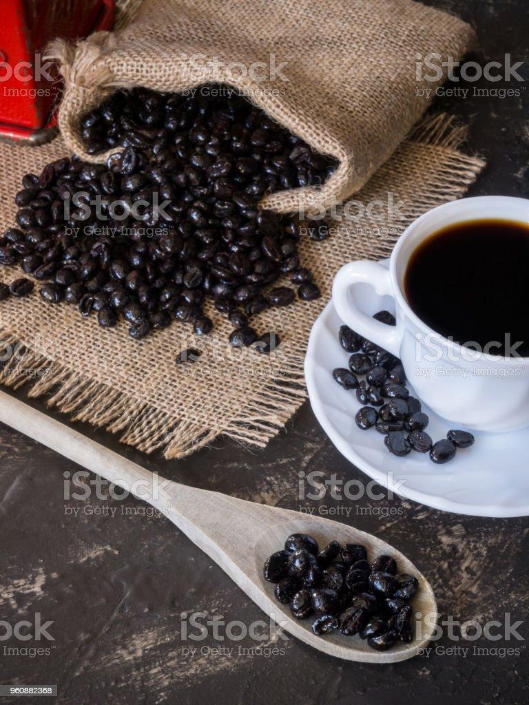Tasse und Tasche mit Kaffeebohnen aus der Tasche auf den steinernen Tisch und Holzlöffel - Lizenzfrei Alt Stock-Foto