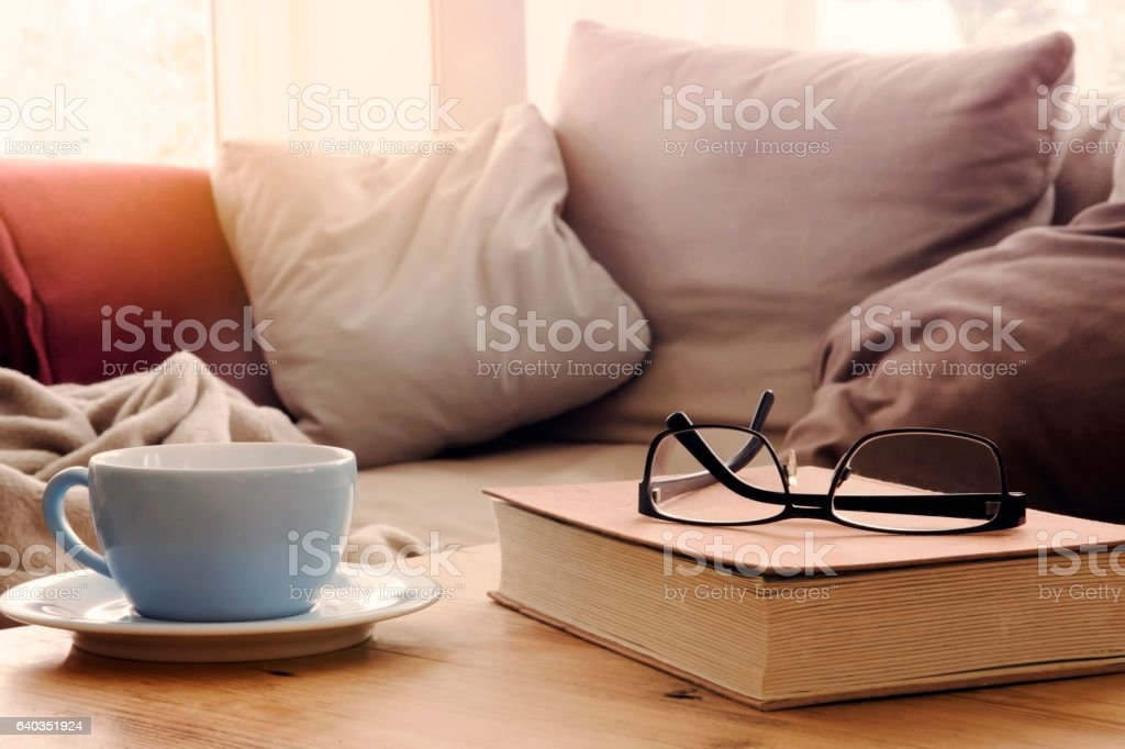 cup and book on table in front of sofa stock photo