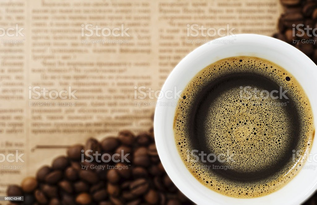 Cup and Coffee Beans on newspaper background royalty-free stock photo