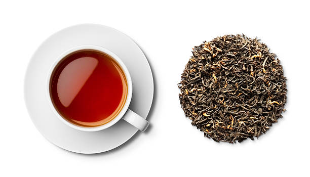 Cup and saucer of Assam tea and leaves from overhead stock photo