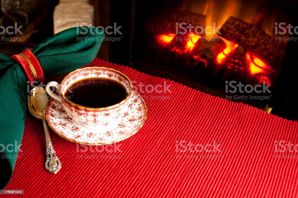 Cup and saucer of coffee by the fireplace royalty-free stock photo