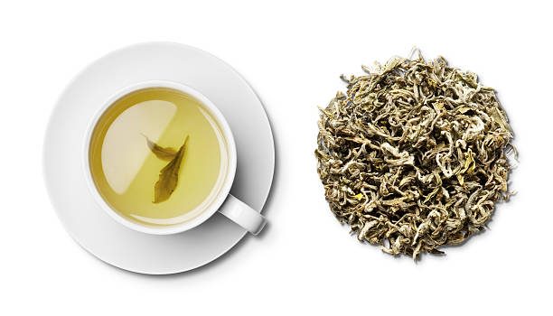 cup and saucer of green tea and leaves overhead - tea leaf stock photos and pictures