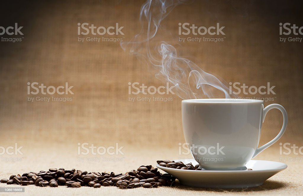 A cup and saucer of hot coffee with fresh beans stock photo
