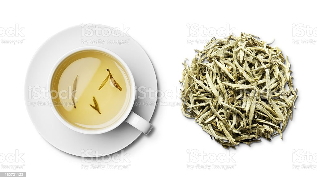 Cup and saucer of Jasmine tea and leaves overhead stock photo