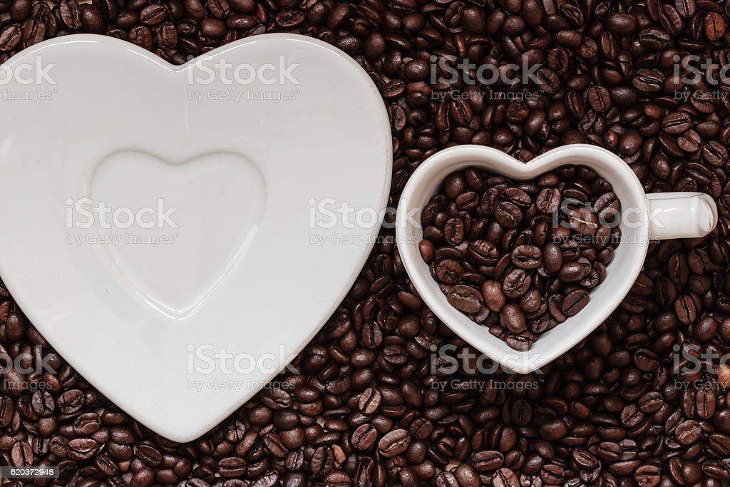 Xícara e Pires sobre fundo de grãos de café foto de stock royalty-free
