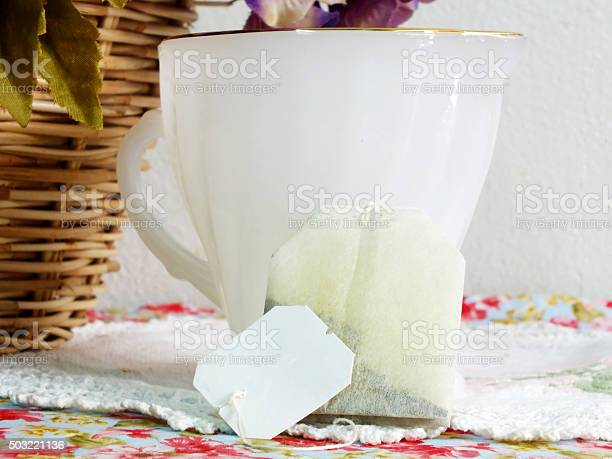 cup and tea bag on tablecloth background