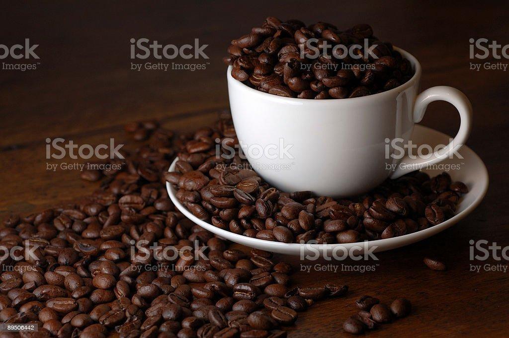 Tasse de café avec les grains de café débordant de photo libre de droits