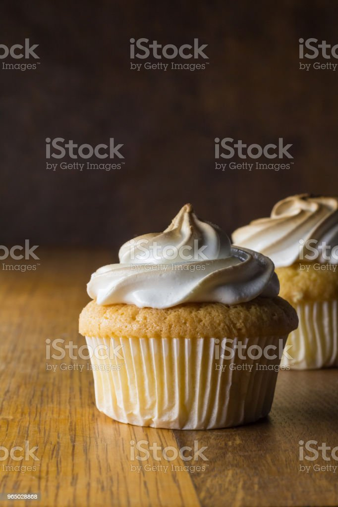 Cup cakes with white frosting on wooden table, focus on front cupcake royalty-free stock photo