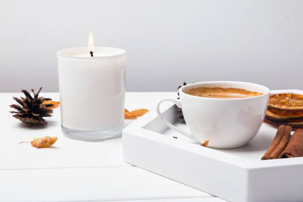 tasse, cinnamin, trockene orangen und blätter und brennende kerze nahaufnahme - herbst kerzen stock-fotos und bilder