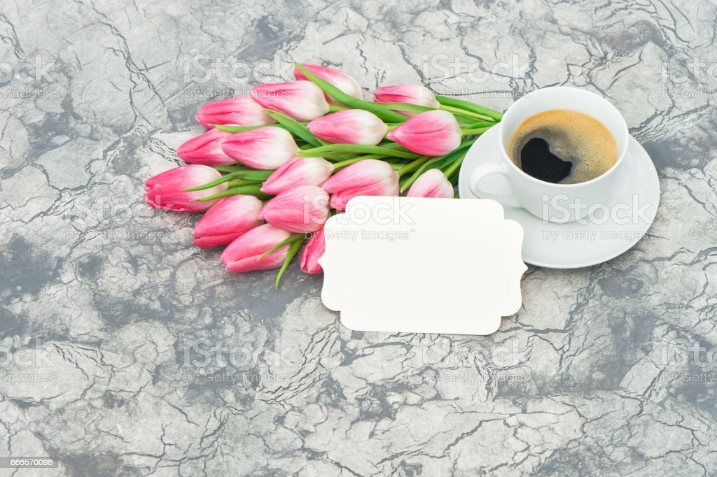 Cup of coffee with tulip flowers and white paper tag
