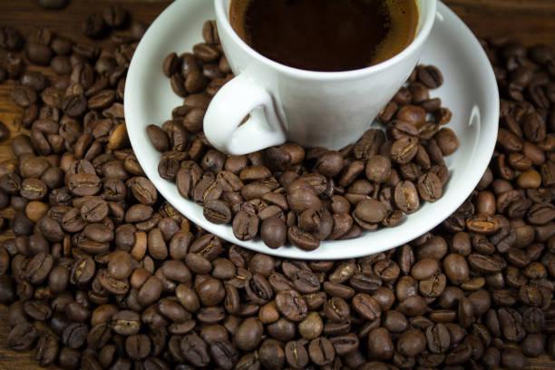 eine tasse voll kaffee kaffeebohnen auf einem teller und tisch aus holz - mokkatassen stock-fotos und bilder