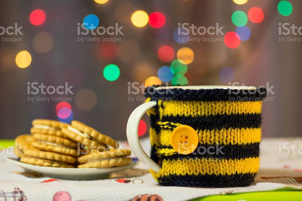 Cup in the knit cover and biscuits background of lights stock photo