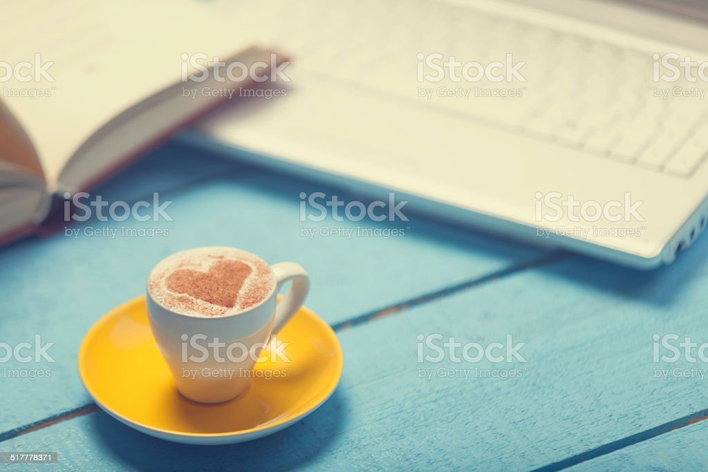 Cup, laptop and book on a wooden table. stock photo