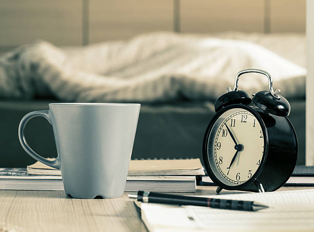 Cup mug and  retro alarm clock on the table stock photo