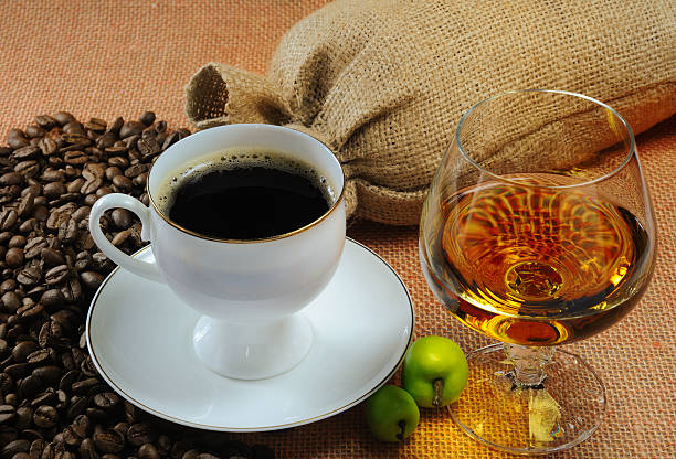 Cup of black coffee and saucer, and glass of alcohol Cup of coffee, cognac glass and bags of coffee beans caffeine stock pictures, royalty-free photos & images