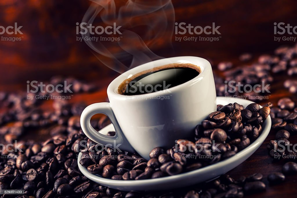 Cup of black coffee and spilled coffee beans stock photo