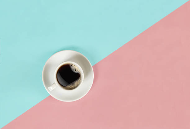 A cup of black coffee on blue and pink background. View from above stock photo