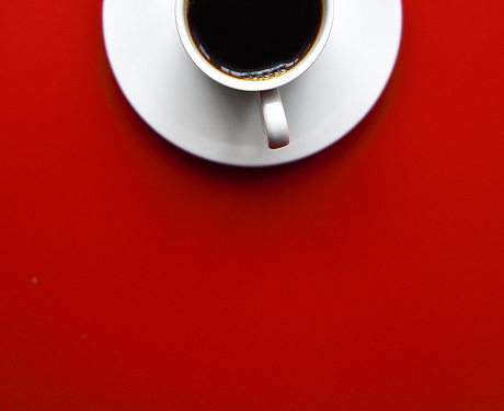 cup of black coffee on red background