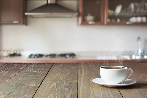Cup of black coffee on wooden tabletop in blurred modern kitchen. Close up. Indoors.