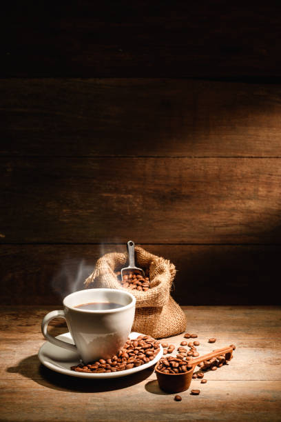 A cup of black coffee or americano with roasted coffee bean in bag, good coffee for health is black coffee without sugar and milk stock photo