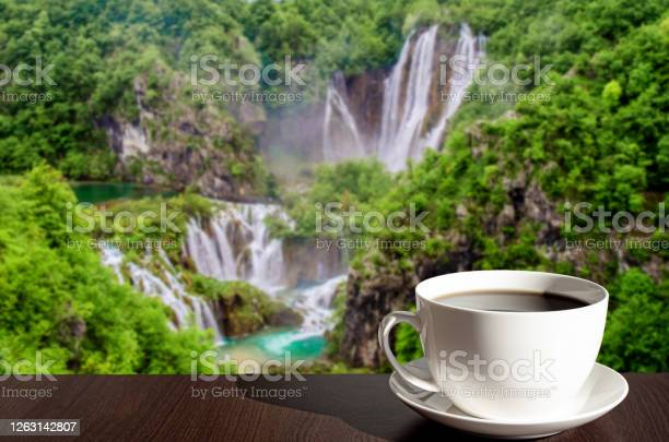 Photo of Cup of black coffee or tea with big waterfall background in Croatia
