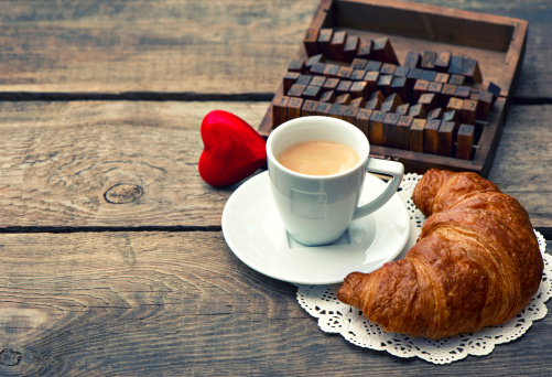 istock Cup of black coffee with croissant and red heart 475464349