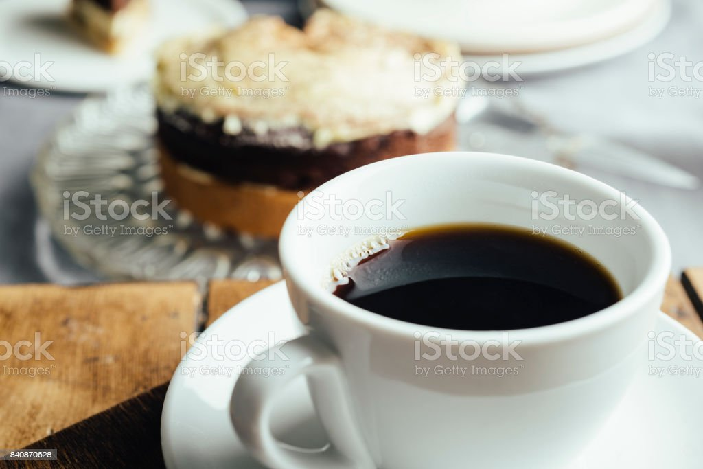 cup of black coffee with defocused cake in the background. stock photo
