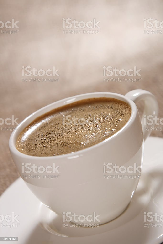 Cup of black coffee with froth on brown background royalty-free stock photo